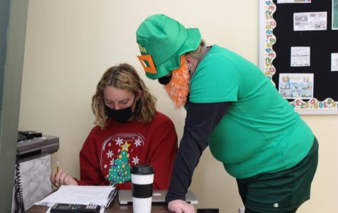 Math teacher Kristin Hilgenfeld, dressed up as a leprechaun, helps senior Olivia Shively with her math questions on Oct. 2.