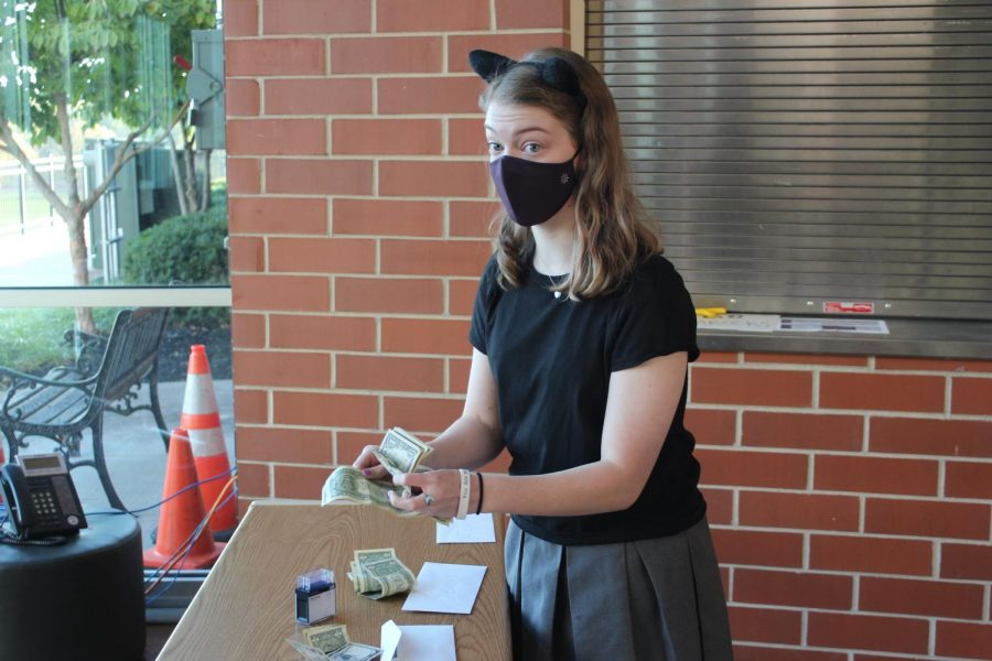 Junior Tess Tappan counted and collected money at the gym entrance as students paid to wear their costumes Oct. 30.