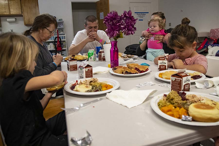 The Swisher family prays before eating Thanksgiving dinner at a church shelter where they have been staying after losing their home in Paradise, Calif., in the Camp fire, on Thursday, Nov. 22, 2018, in Chico, Calif. (Gina Ferazzi/Los AngelesTimes/TNS)