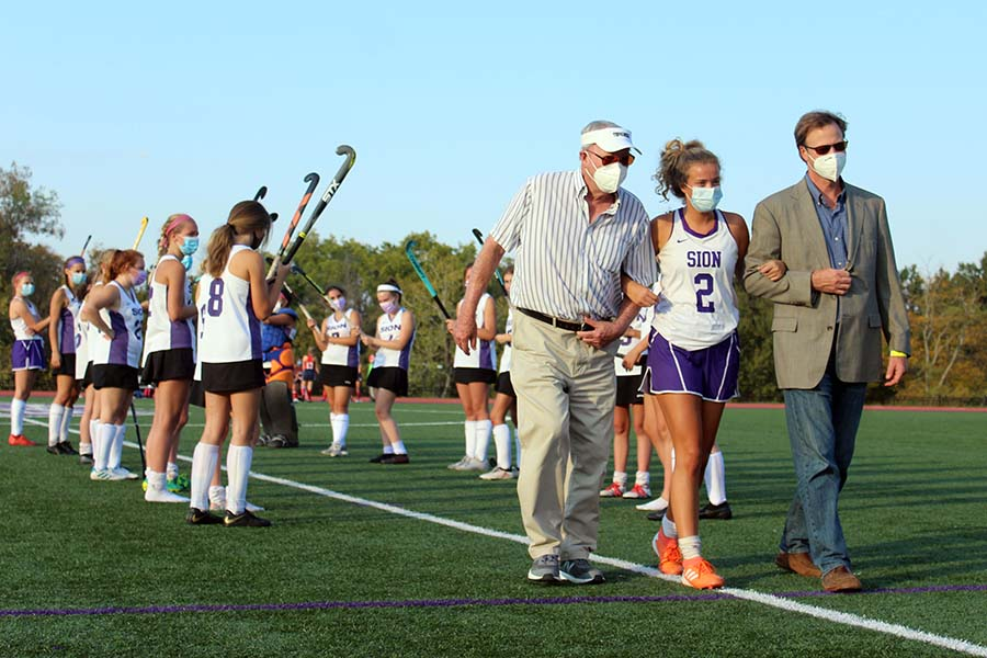 Senior Ruby Wright walks with her father and her grandfather while being presented during the field hockey Senior Night on Sept. 10. on the field.