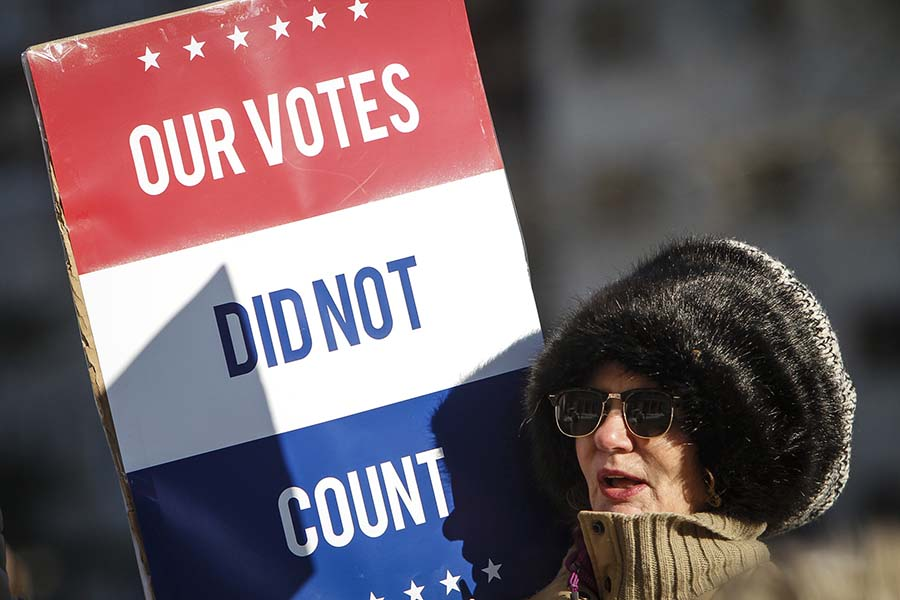 "LANSING, MI - DECEMBER 19: Jane Dailey, of Lansing, protests President-elect Donald Trump at a rally at the Michigan State Capitol before the state electoral college met to cast their votes on December 19, 2016 in Lansing, Michigan, United States.  ""I know it won't change anything but I had to do something,"" Dailey said.  The electoral college met in the afternoon and voted unanimously for Trump. Electors from all 50 states cast votes today in their respective state capitols.  (Photo by Sarah Rice/Getty Images)"
