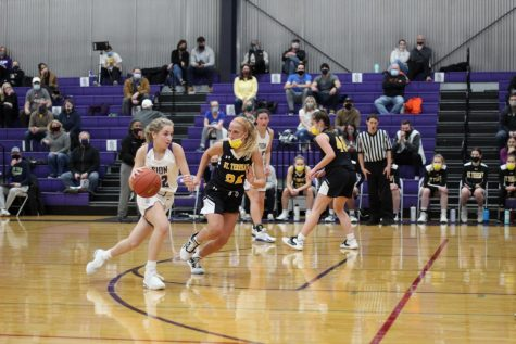 Senior Katelyn Brinkman attempts to escape her guard, Junior Grace Quinn, by dribbling down the lane.