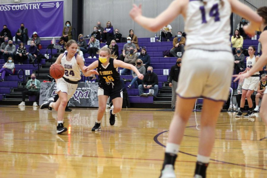 Senior Katelyn Brinkman drives the ball to the hoop during the varsity basketball game against St. Teresa's Academy on Jan. 5.