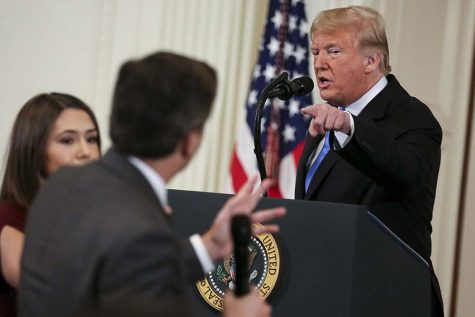 A White House staff member, left, tries to take away the microphone from CNN White House correspondent Jim Acosta during an exchange with President Donald Trump on Wednesday, Nov. 7, 2018, in Washington, D.C. (Oliver Contreras/Sipa USA/TNS)