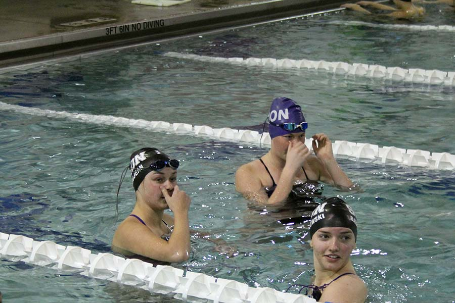 Seniors Emma Grojean, Kate Vankeirsbilck and Elicia Baranowski chat during their warm ups before the swim and dive meet against St. Teresas Academy at the Red Bridge YMCA on Jan. 26.