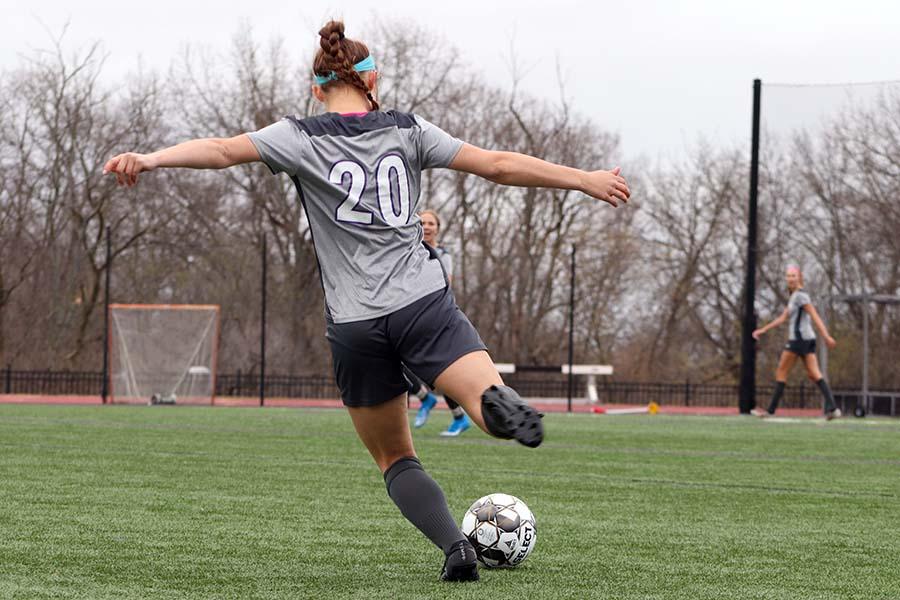 Freshman Jane Lehmann kicks the ball up the field to her teammates March 23.