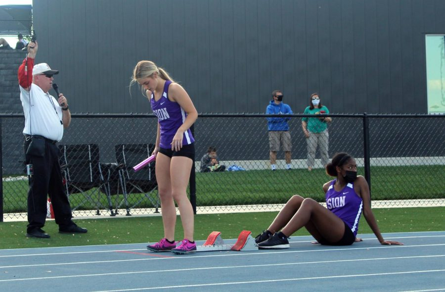 Sophomore+Makaila+Traylor+helps+senior+Paxton+Misemer+prepare+for+the+4x200+relay.