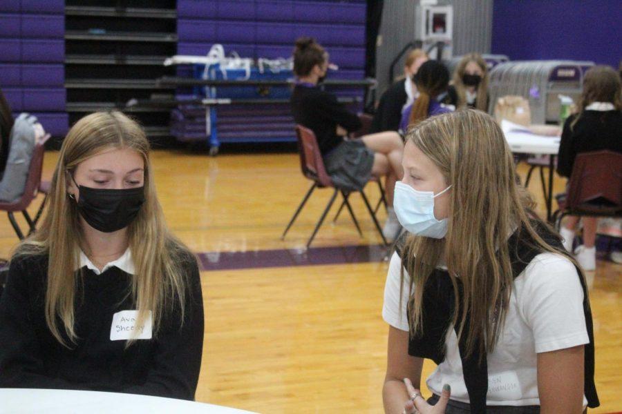 Senior Lauren Ellwanger and freshman Ava Sheedy chat during ice breaker activities at freshman orientation on Aug. 20.