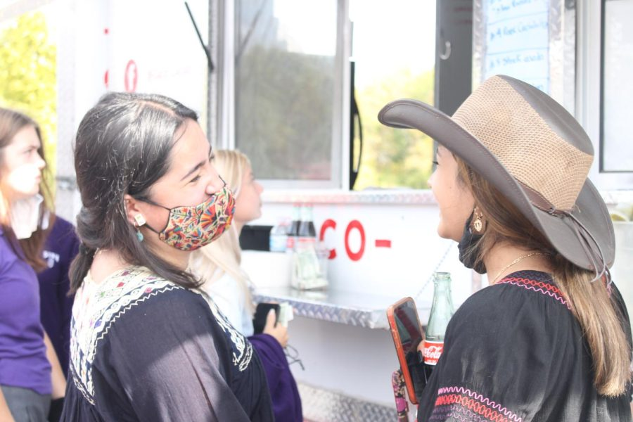 Junior Samy Mora Cuevas laughs with senior Vivi Calderon while waiting for their tacos in front of the Taco Cacao taco truck.