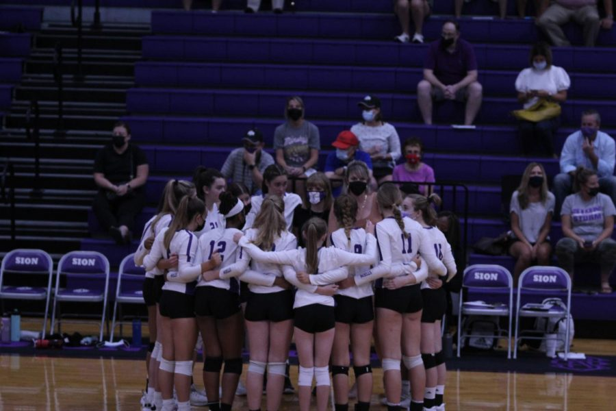 Varsity+huddles+after+their+first+match+to+regroup+and+make+their+comeback+in+the+following+three+sets.