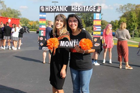 Social Sciences teacher Morey Williams and Spanish teacher Señora Gonzalez pose holding the Hispanic Heritage Month sign in the circle drive.